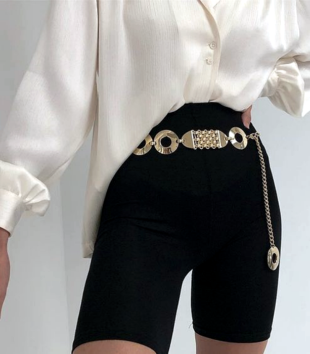 white satin blouse with loose sleeves, black cycling shorts with metallic gold belt