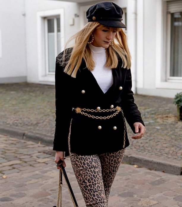 blonde girl with black hat, black jacket with metallic gold belt, white top with high neck, brown animal print pants