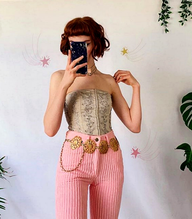 redhead girl with beige sleeveless corset, pink corduroy pants and gold metallic belt with soles