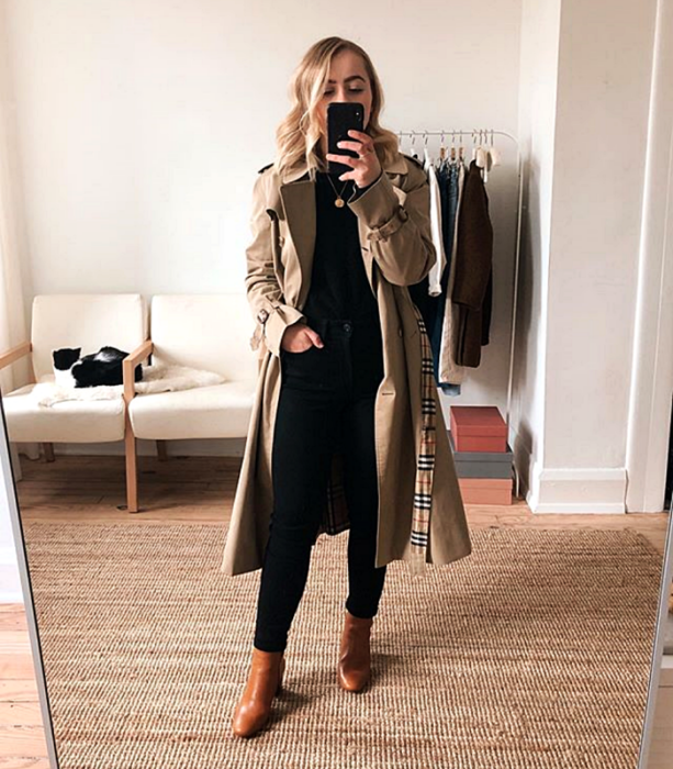 blonde girl wearing brown trench coat, black top, black skinny jeans, brown leather ankle boots