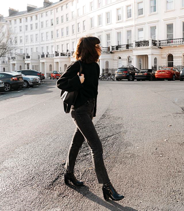 short black hair girl wearing black sweater, black handbag, dark skinny jeans and leather high heel ankle boots