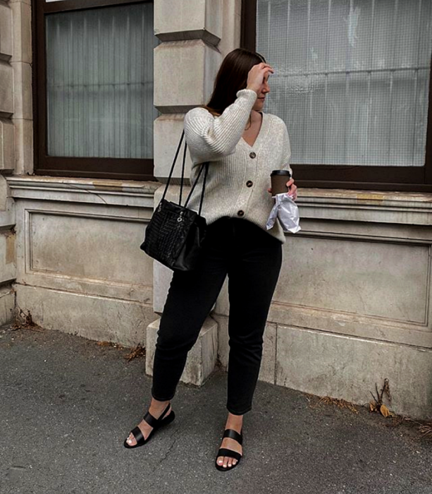blonde girl wearing a white cardigan, black skinny jeans, black flat sandals and black small bag