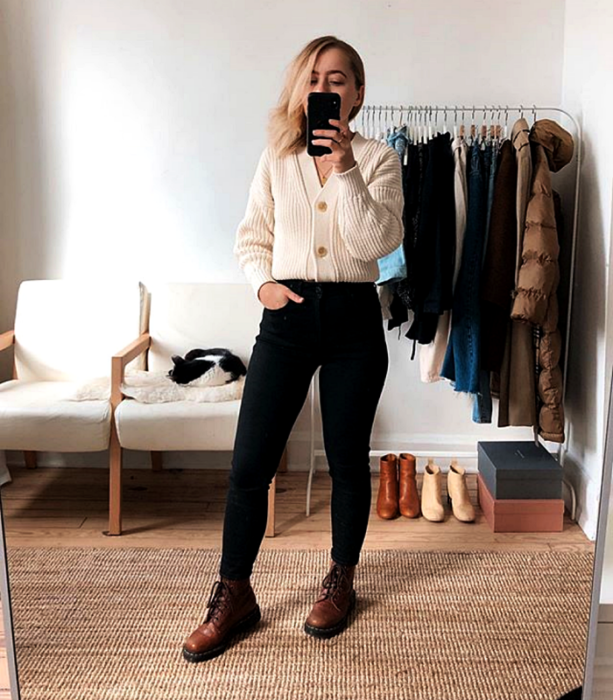 blonde girl wearing a white cardigan, black skinny jeans, brown floor boots