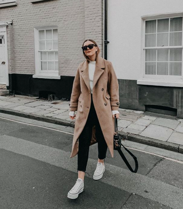 blonde girl wearing sunglasses, white sweater, light beige coat, black skinny jeans and white converse sneakers