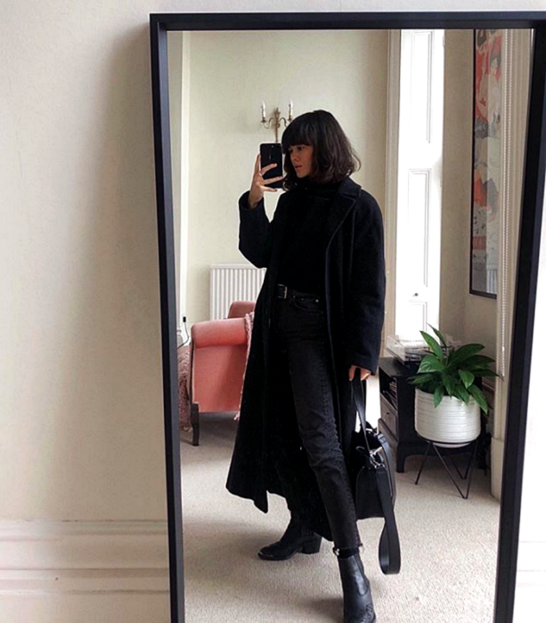 black short hair girl wearing black high neck top, long black coat, black dark skinny jeans and black fur heeled ankle boots