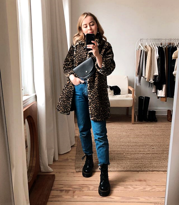 blonde girl wearing long animal print coat, black leather fanny pack, skinny jeans and black floor boots