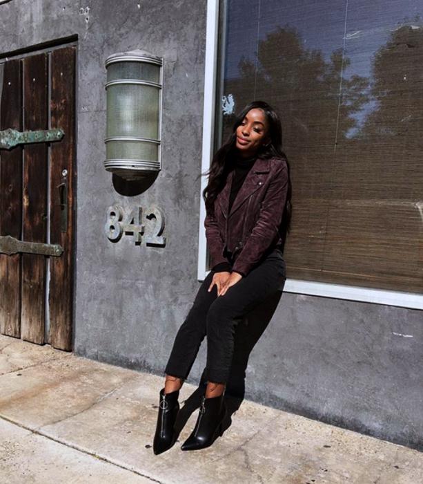 chica morena de cabello negro usando una chaqueta morada, top negro, skinny jeans oscuros y botines negros de piel