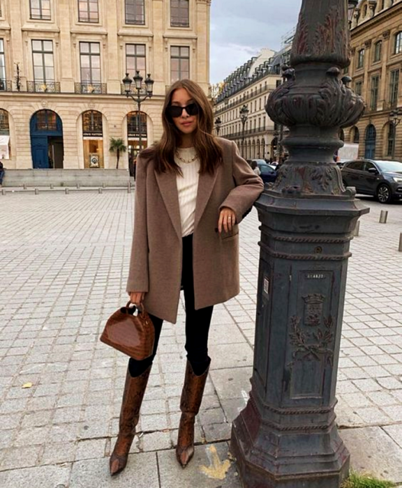 brown haired girl wearing sunglasses, white top, large brown blazer coat, black skinny jeans and long brown leather boots with heel and brown handbag