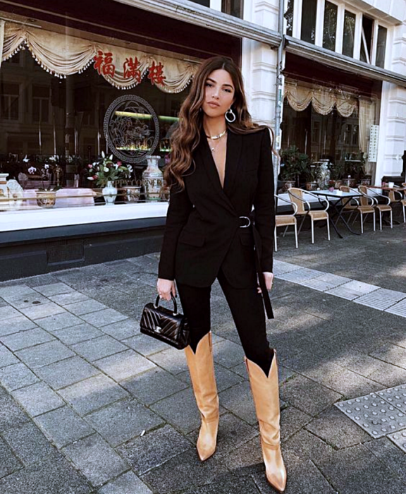 brown haired girl wearing black blazer jacket, black skinny jeans, brown long boots and small black tote bag