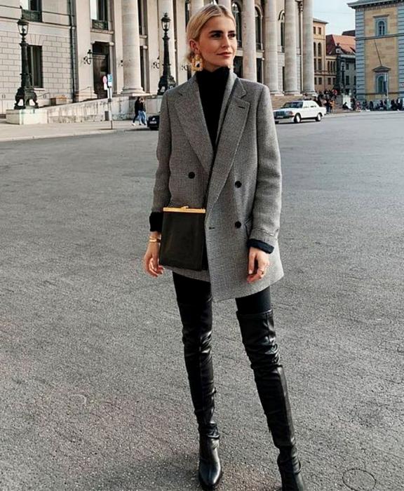 blonde girl wearing black high neck top, oversized gray blazer, black bag, black leggings, black leather long boots
