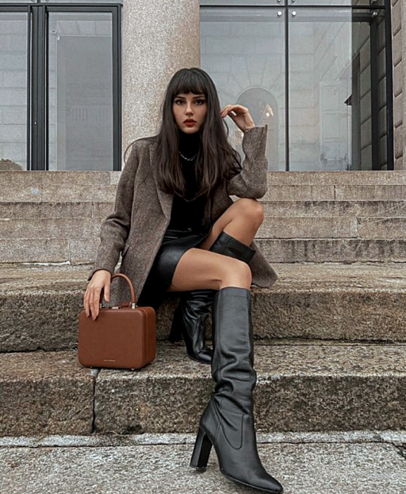 long brown hair girl wearing black turtleneck top, long brown blazer, leather mini skirt, long leather heeled boots and brown clutch bag