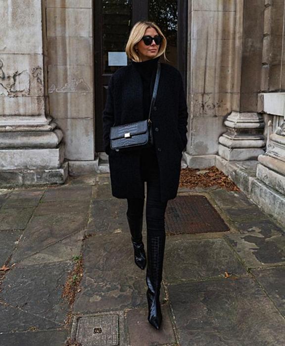 blonde girl with sunglasses wearing black high neck top, black long coat, black handbag, black leggings, long leather boots with heel