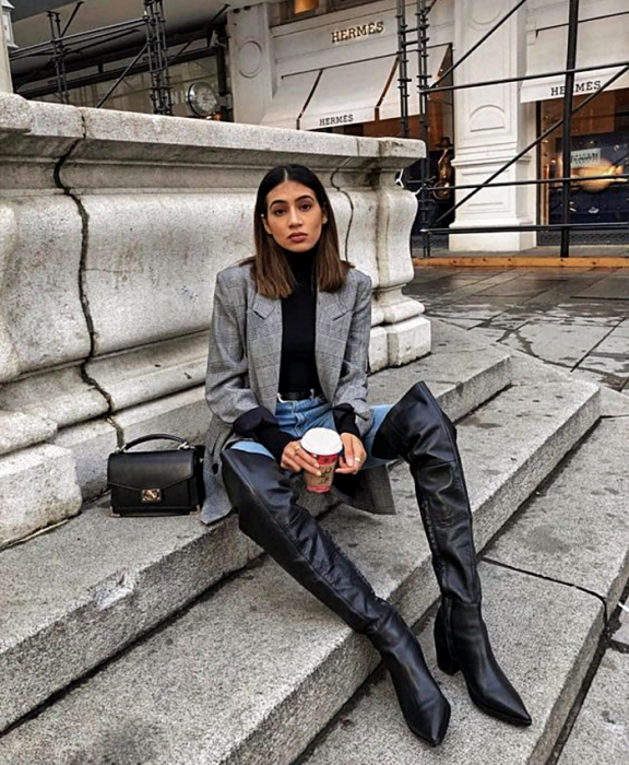 brown haired girl wearing a black high neck top, gray blazer oversized jacket, waist jeans, long leather heeled boots, and black handbag