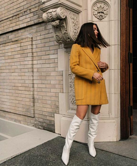 chica morena con blazer oversized amarillo y botas largas blancas de cuero