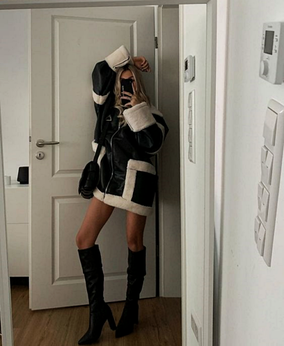 blonde girl taking a selfie wearing a black coat with white, black handbag and long black high heel boots