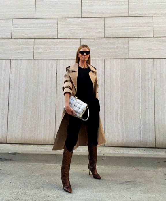 blonde girl with sunglasses, beige coat, black top, black pants, brown leather long boots and white big bag
