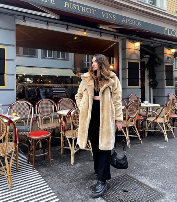 girl with long light hair in long beige teddy coat, black crop top, black dress pants and thick-soled leather boots and black mini handbag