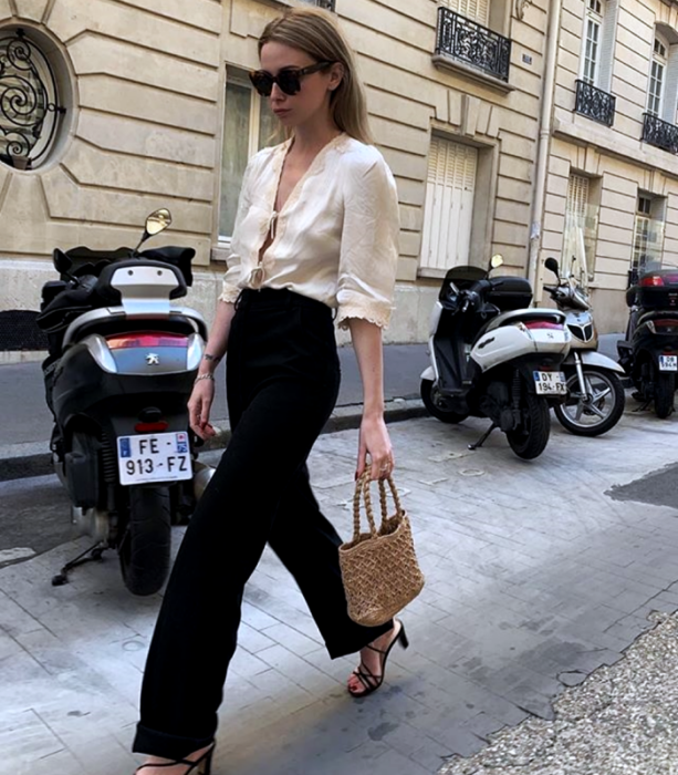 blonde girl with sunglasses, long-sleeved cream blouse, black dress pants, black heeled sandals and small raffia bag