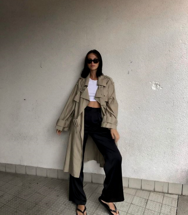 brown haired girl wearing sunglasses, white crop top, beige coat, black dress pants and black sandals