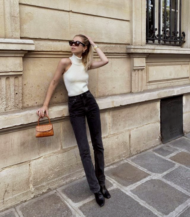 blonde girl with sunglasses, sleeveless high neck white knit top, black waist jeans, black ankle boots and orange mini bag