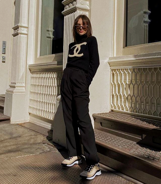 chica con cabello castaño usando lentes de sol, suéter negro con logo de chanel, pantalones negros de vestir, tenis deportivos beige con negro y suela blanca