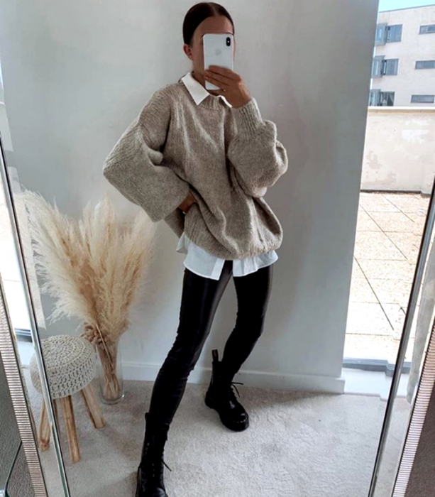 brown haired girl wearing white dress shirt, beige oversized sweater, black leather leggings and black chunky sole ankle boots