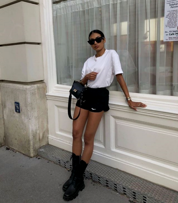 Brown haired brunette girl wearing sunglasses, white t-shirt, short black shorts, leather mini bag, long thick-soled ankle boots