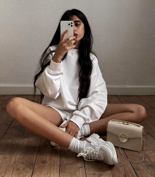 girl with long brown hair wearing white sweatshirt, white shorts, white sneakers and white beige bag taking a selfie
