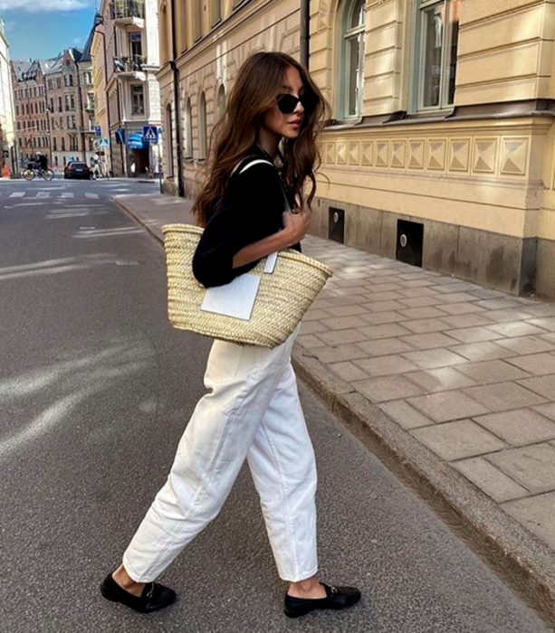 girl with long brown hair in sunglasses, black sweater, large raffia knitted bag, baggy white jeans and black loafers