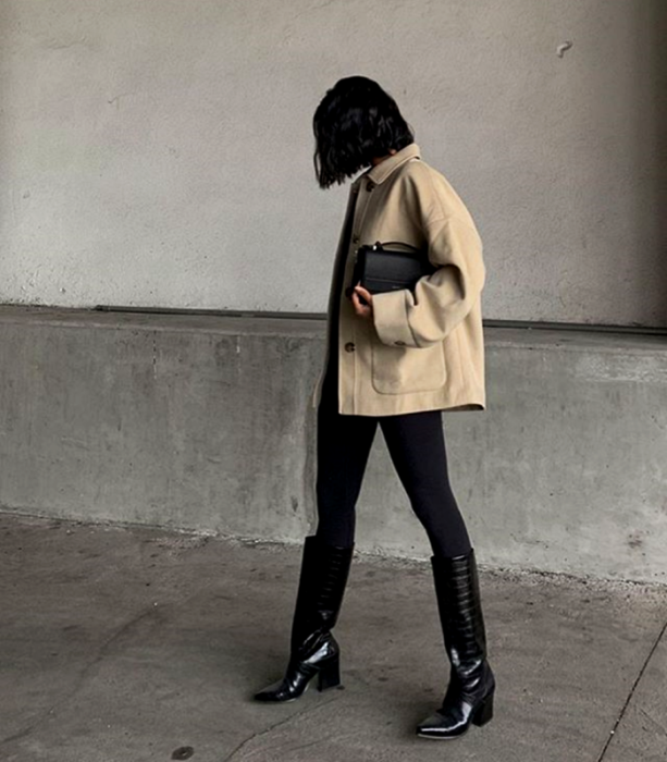 short dark hair girl wearing beige oversized jacket, black mini clutch bag, black leggings and long leather heeled boots