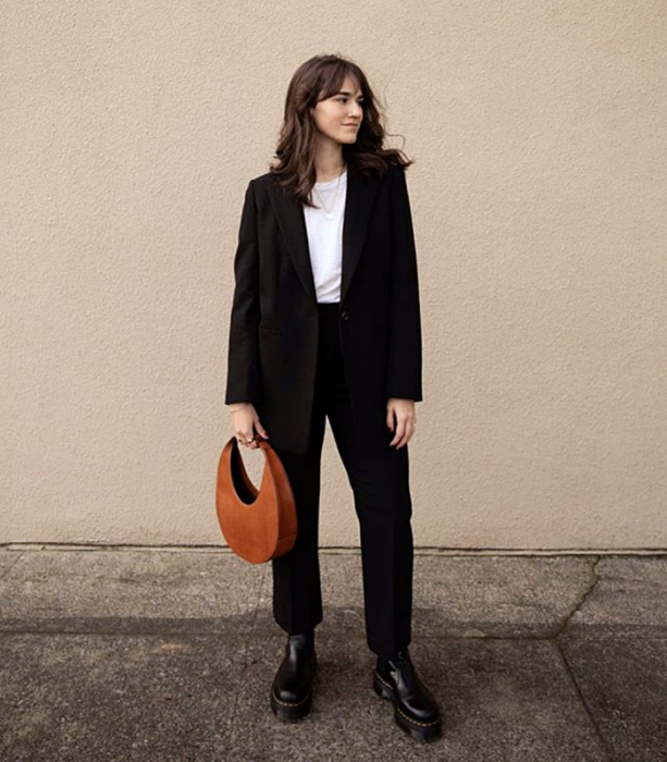 brown haired girl wearing a white t-shirt, black blazer, black dress pants, black chunky soled boots and orange tote bag