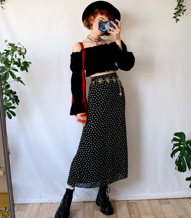 red haired girl wearing black hat with large brim, black off shoulder long sleeve crop top, black skirt with white polka dots, black floor boots, red tote bag and gold metallic belt