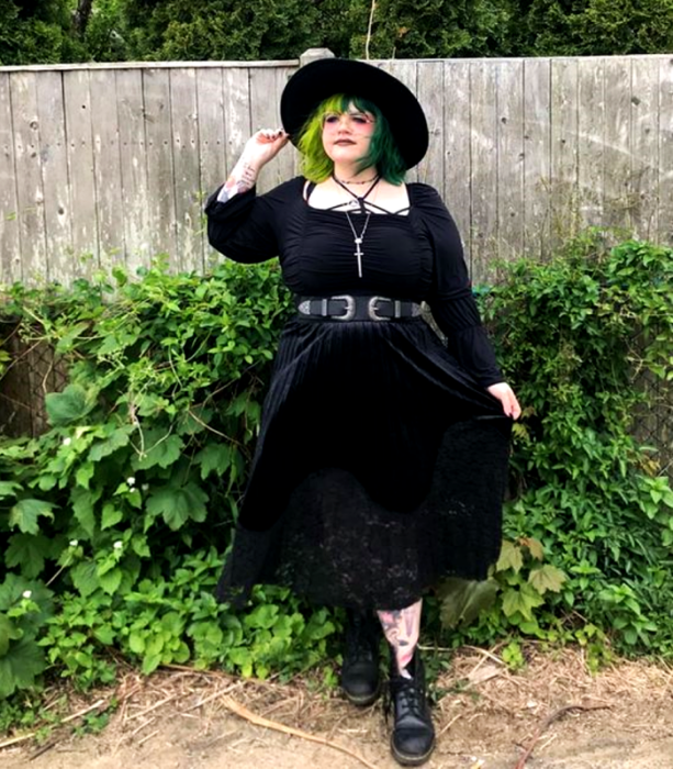 green haired curvy girl wearing black large brimmed hat, black midi dress with square neckline, 3/4 sleeves and black belt, black leather heelless ankle boots