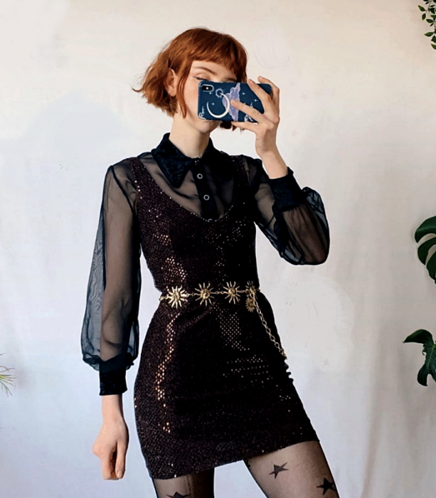 red-haired girl wearing a short purple sequined dress, black semi-sheer blouse with long sleeves and shirt collar, black stockings with stars and gold metal belt; witchy style outfit