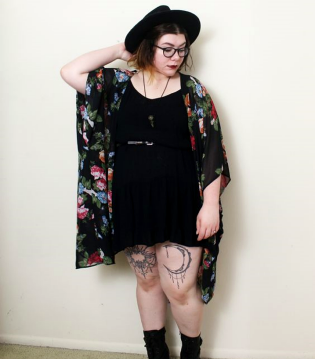 curvy girl wearing glasses, black hat with large brim, black mini dress with black belt, black ankle boots and black kimono with flowers; witchy style outfit