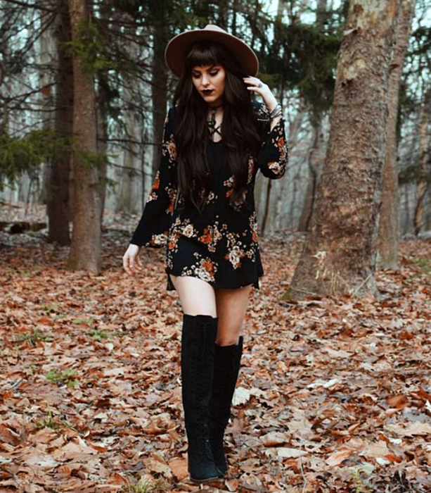 long brown hair girl wearing brown big brimmed hat, black mini dress with red flowers, long black floor boots; witchy style outfit