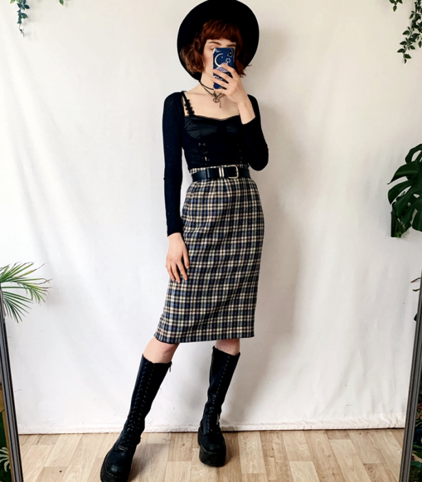 redhead girl wearing black large brim hat, long sleeve black bustier top, plaid waist midi skirt with black belt, black leather long boots