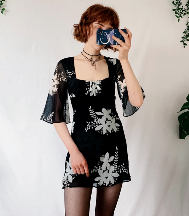 redhead girl wearing a black mini dress with gray flowers, 3/4 sleeve with black stockings