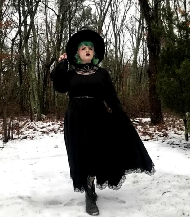 chica curvy de cabello verde usando un sombrero de ala grande negro, vestido largo negro con mangas largas y amplias, botines negros y cinturón negro; outfit estilo witchy