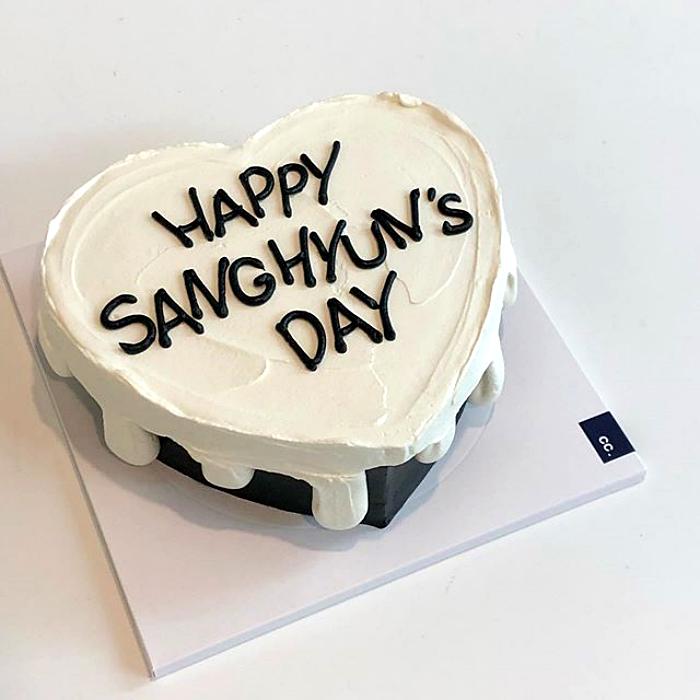 pastel blanco en forma de corazón diseño minimalista con negro debajo y letras de feliz cumpleaños con betún negro