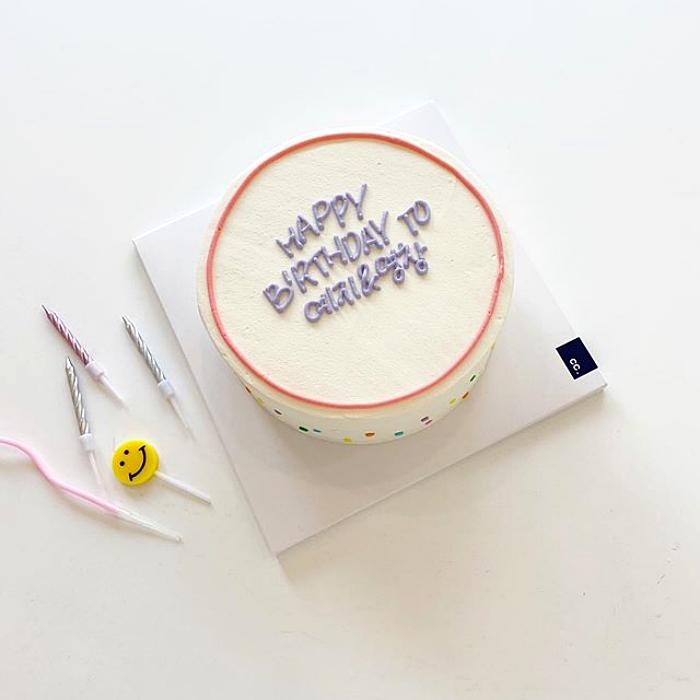 pastel blanco minimalista con letras lilas de feliz cumpleaños y círculo simétrico en color rosa claro