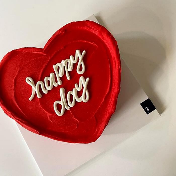 pastel minimalista en forma de corazón rojo con feliz día en letras blancas