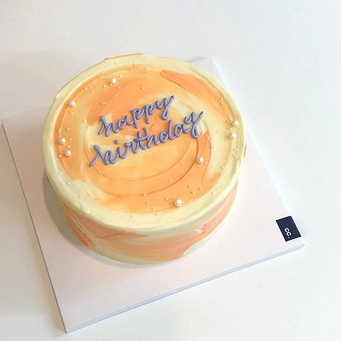 pastel amarillo minimalista con betún naranja y amarillo con letras azules de feliz cumpleaños