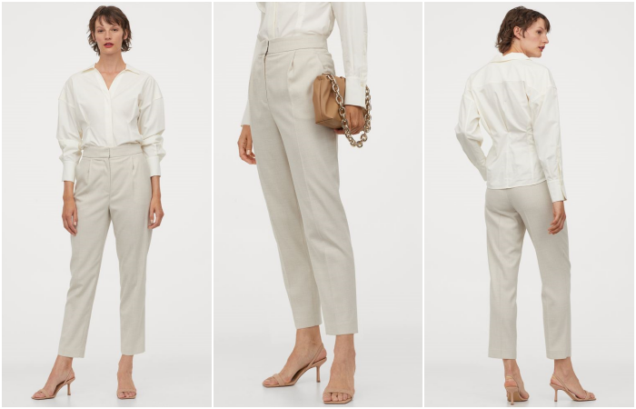 short-haired girl wearing a white long-sleeved button-down shirt, straight beige dress pants, beige clutch bag and beige high-heeled sandals