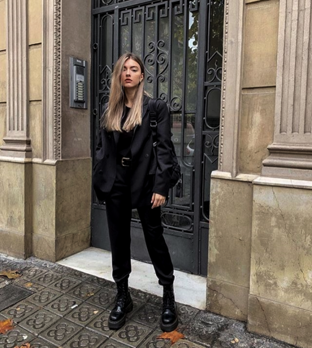 blonde girl wearing a black top, black jacket, black dress pants, black leather boots and black small bag