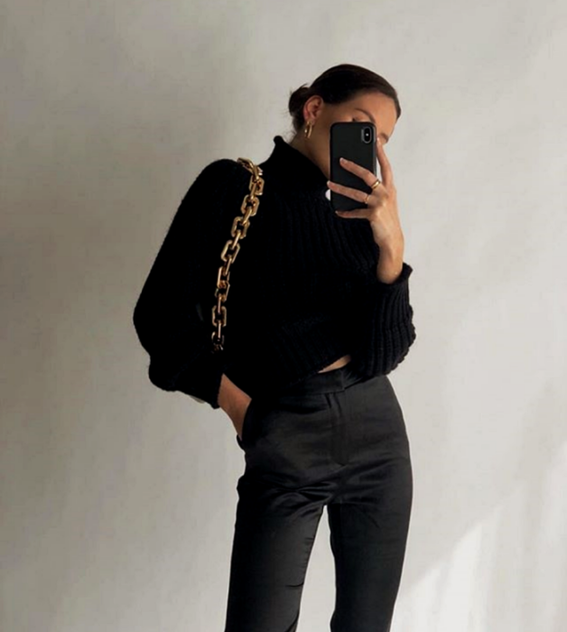 brown haired girl wearing black turtleneck sweater, black dress pants and gold chain strap bag