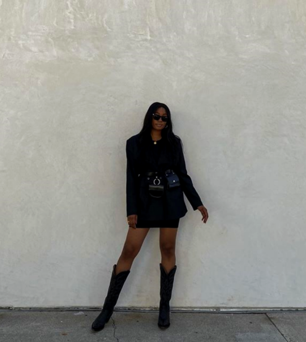 brunette girl wearing sunglasses, black oversized jacket, black skirt, long cowboy-style leather boots and black leather bag at the waist