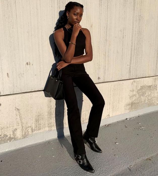 chica morena usando top halter negro, jeans rectos negros, botines de punta en pico negros y bolso mini negro de cuero