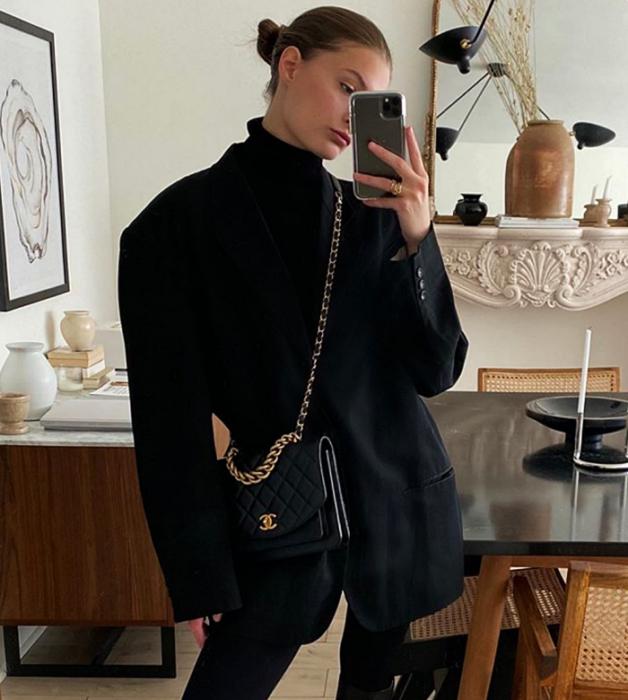 chica rubia, top negro de cuello alto, saco oversized negro, bolso negro de piel y leggings negros