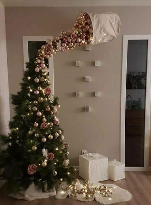 Pinito navideño decorado con esferas doradas cayendo de un saco; ideas para decorar tu arbolito de Navidad